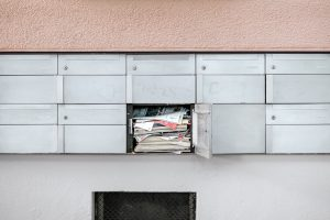 A mail box overflows with newspapers, letters, and more, likely because mail forwarding or address changes weren't set up before moving in Ottawa.