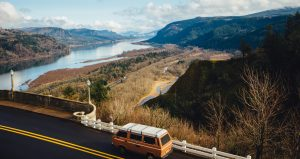 A van sits parked on the side of a road looking over a beautiful river valley, possibly with a driver trying to find something they forgot at the start of their long-distance move.