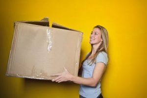 Woman in grey shirt holding brown cardboard moving box.