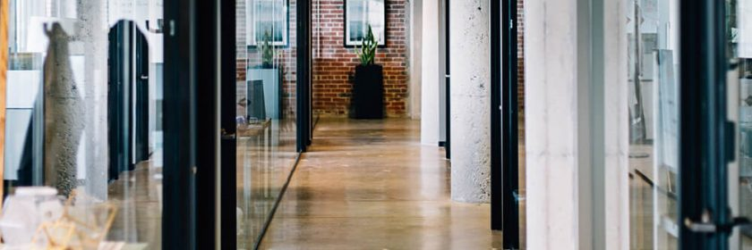 A modern office hallway with concrete pillars and glass walls, looking towards the exit.