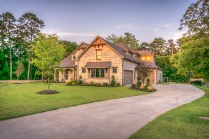 A beautiful home sits at the end of its driveway, lit by the afternoon sun.