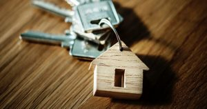 wooden house keychain with four keys on it